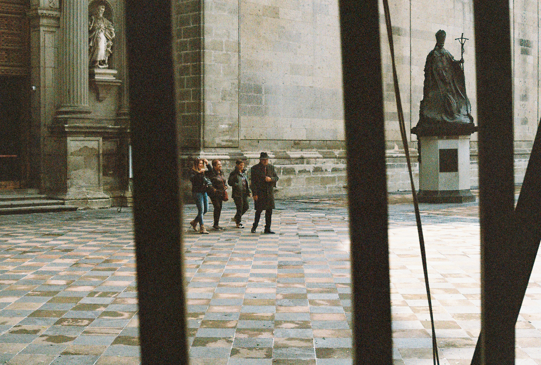 People leaving Mexico City Metropolitan Cathedral shot through the railings by Nick Barry 35mm film.
