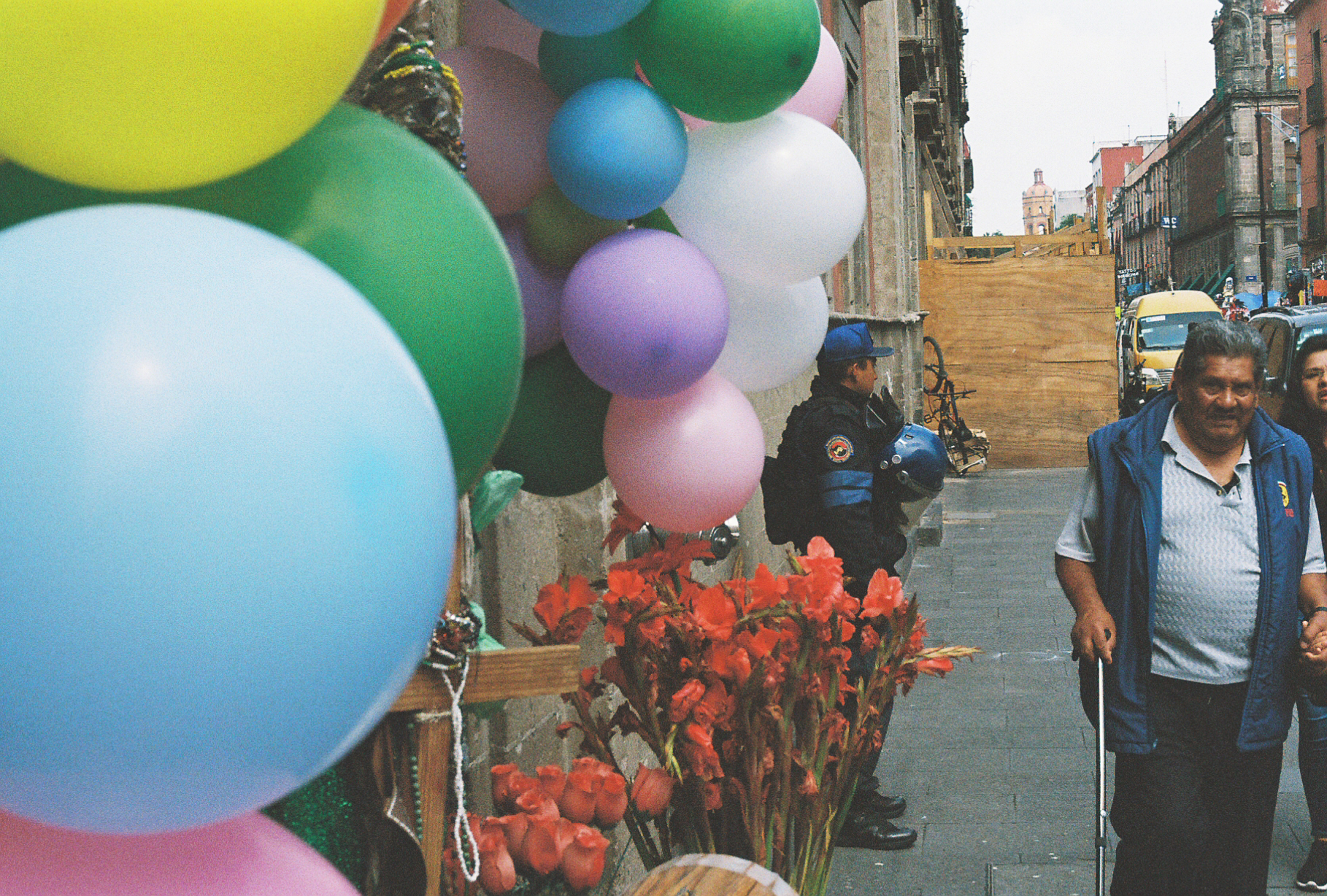 An old man with a cane walks by an abundance of balloons. Mexico City. By Nick Barry