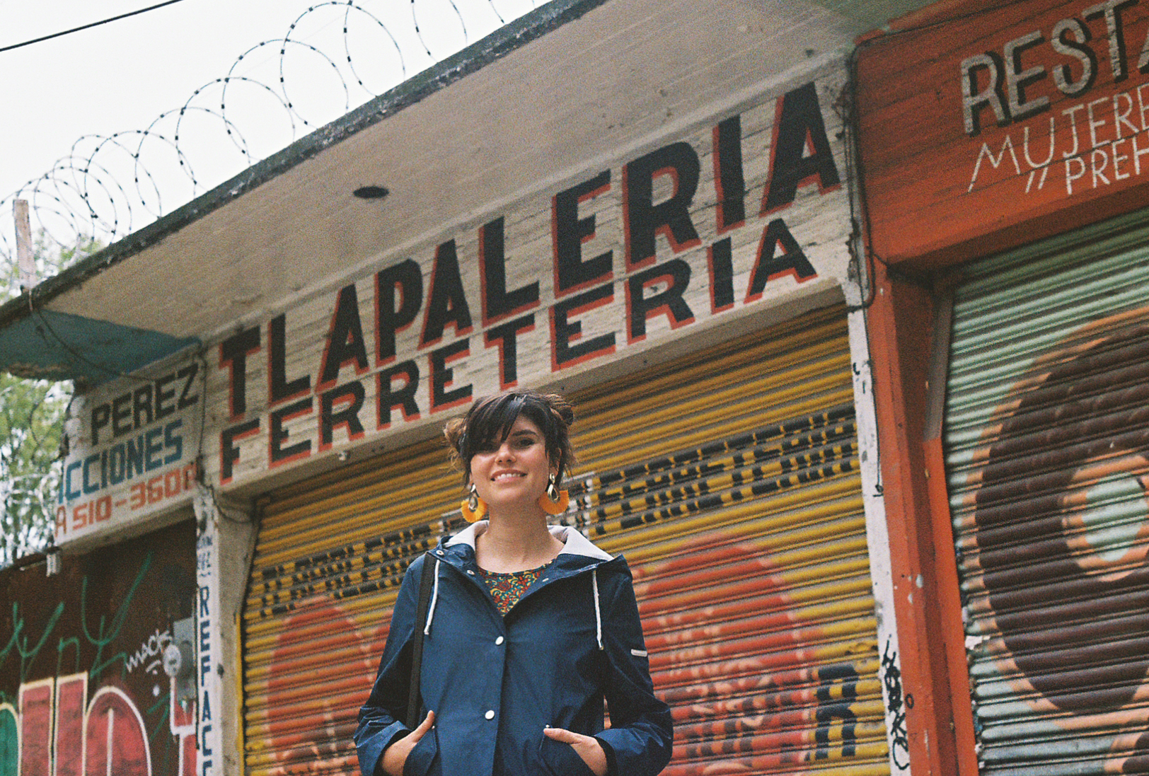 Beautiful lady standing in front of beautiful hand lettered shop fronts, Mexico City. By Nick Barry 35mm film