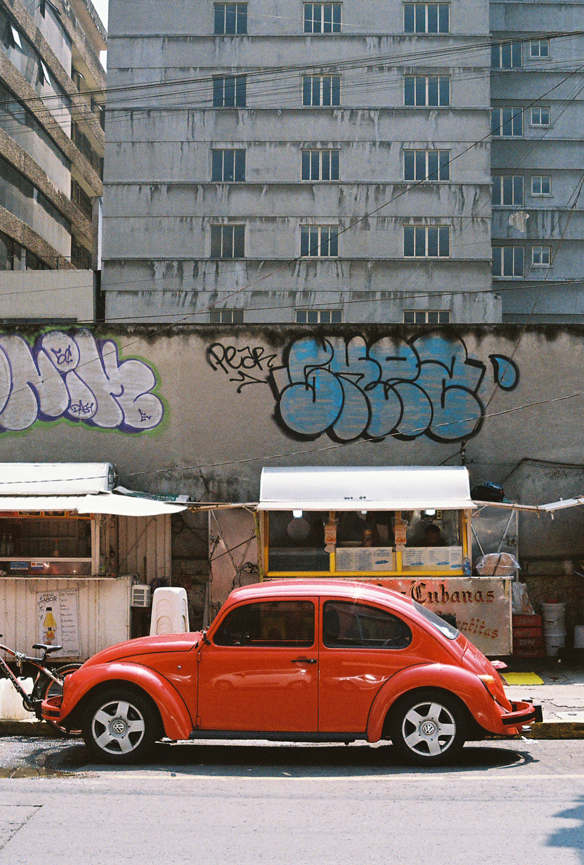 A shiny red Volkswagen Beetle, or bug, in front of some food stands and grey apartment buildings. Mexico City. Photographer Nick Barry.