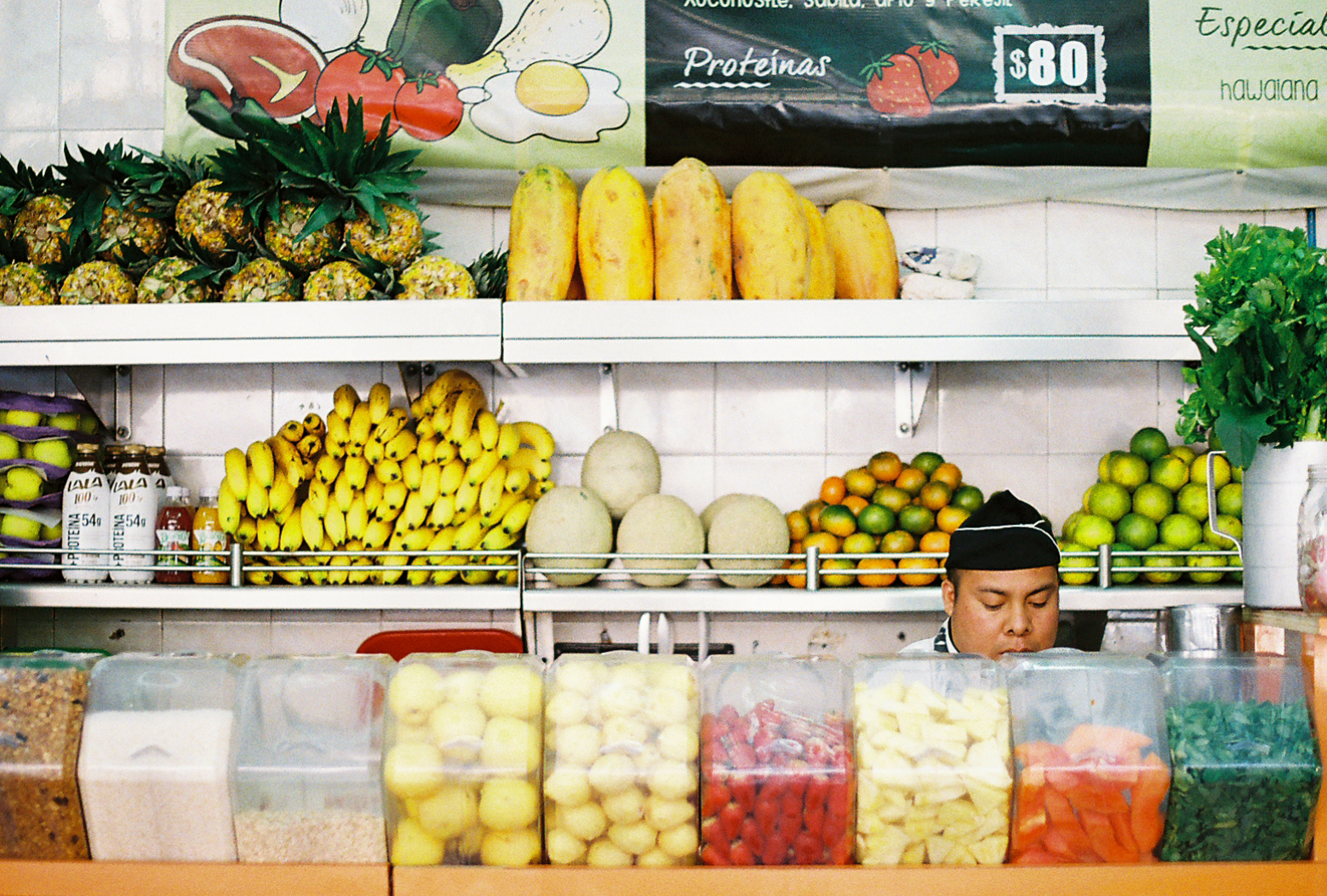 Jugo de Agua. A man behind the counter in front of a wall of fruit in a juice or smoothie store. Mexico City 35mm film. Photographed by Nick Barry