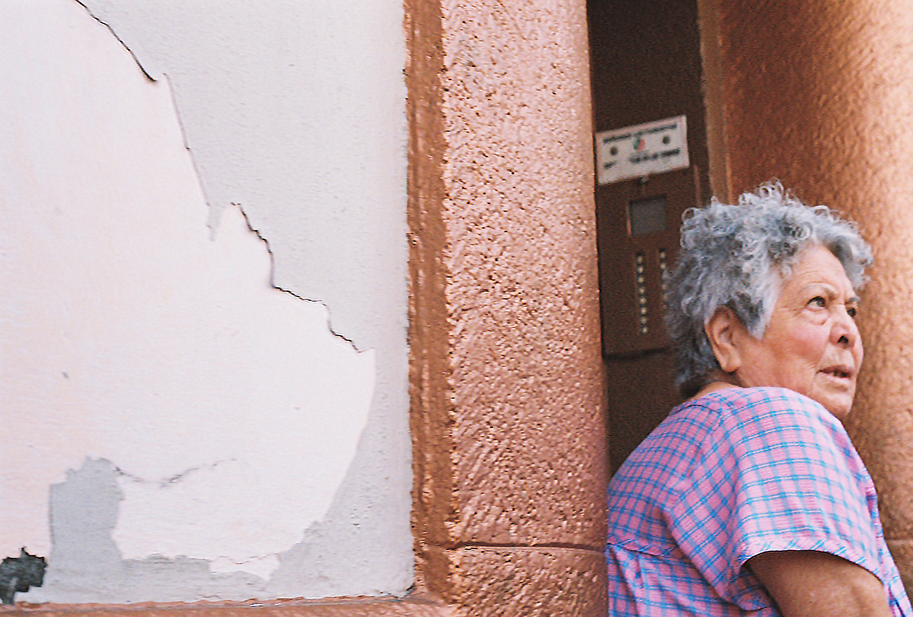 An old lady outside standing in the doorway of an apartment. The paint is peeling off the walls. 35mm film shot by Nick Barry in Mexico City