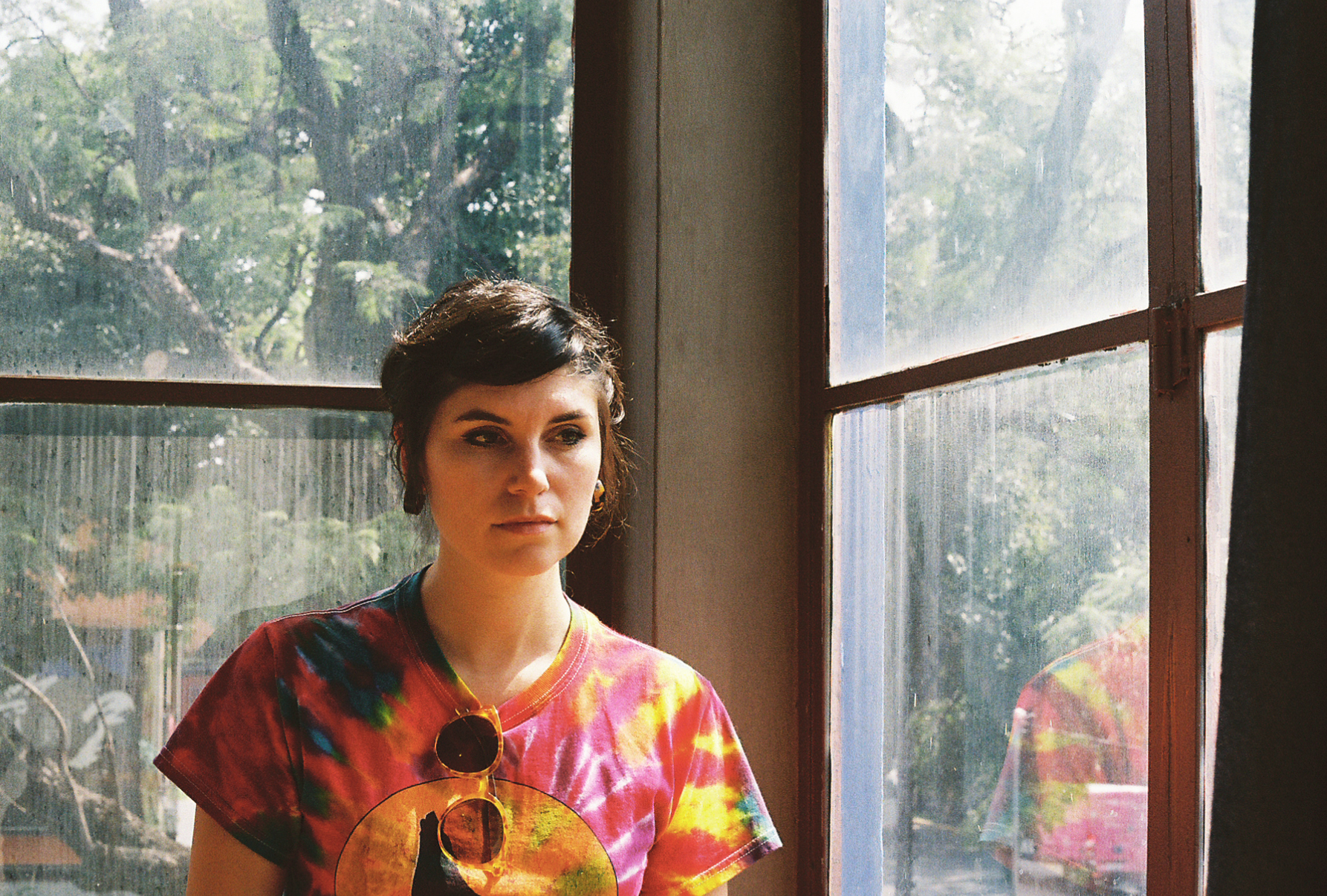 Beautiful woman in tie-dyed shirt looks thoughtful inside the studio home of Frida Kahlo, Mexico City. By Nick Barry