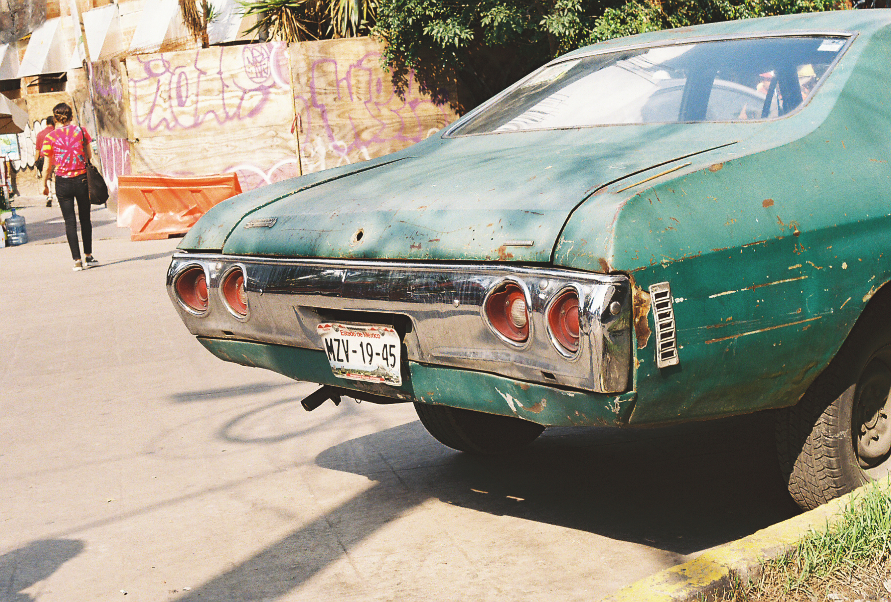 The rear of a large teal rusty classic American muscle car. Mexico City. Photographer Nick Barry