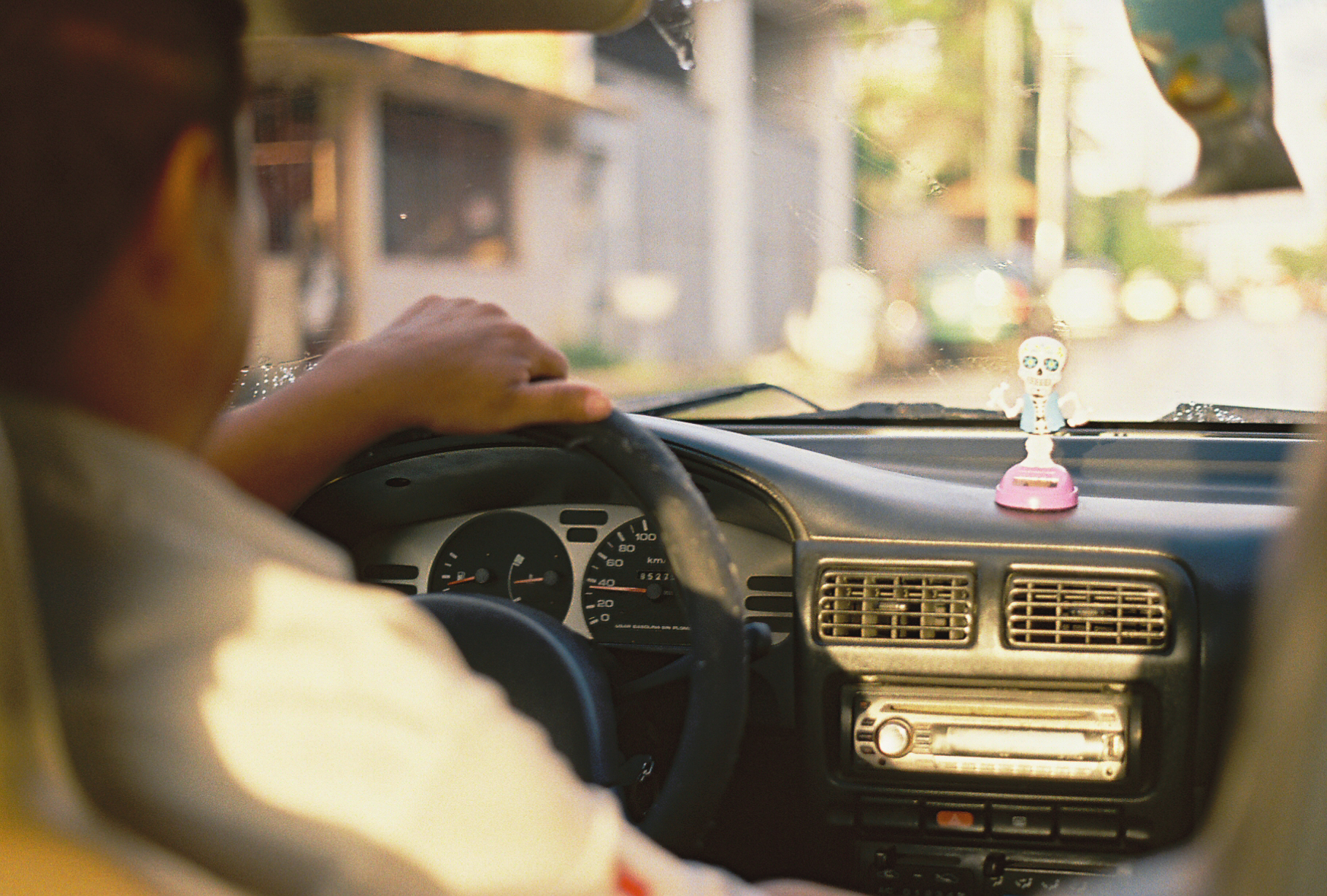 From the back seat of a taxi a little candy skull skeleton dances on the dashboard. Tulum, Mexico. Photographer Nick Barry