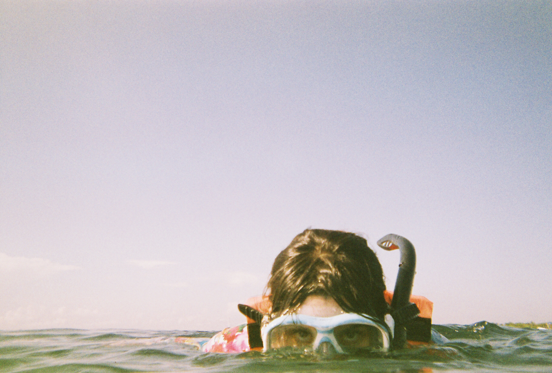 A female's eyes and hair pop out of the water. She's snorkeling in Tulum, Mexico. 35mm. Photographer Nick Barry