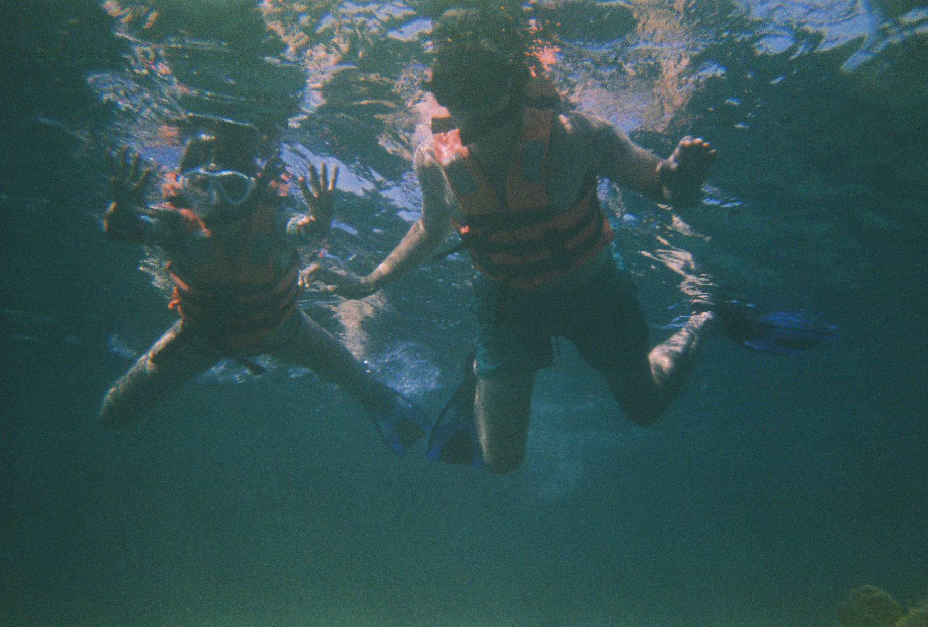 Two people snorkeling, underwater photograph. In Tulum off a coral reef. Old expired 35mm film.